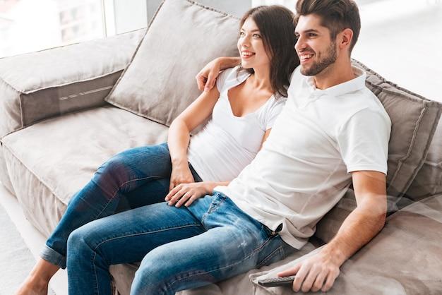 Szczęśliwa zrelaksowana młoda para siedzi na kanapie i ogląda telewizję w domu