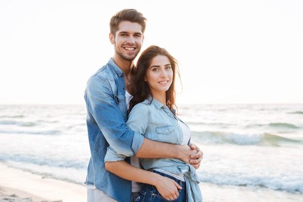 Szczęśliwa zrelaksowana młoda para stojąca i uśmiechająca się na plaży