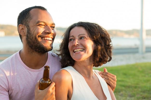 Szczęśliwa zrelaksowana para pije piwo i gawędzi outdoors