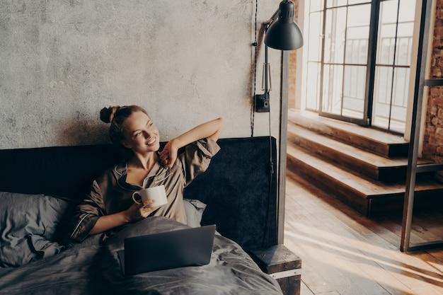 Szczęśliwa zrelaksowana pozytywna młoda dziewczyna freelancer pijąca kawę przed rozpoczęciem zdalnej pracy w domu
