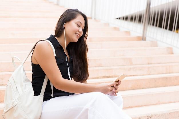 Szczęśliwa zrelaksowana szkoły wyższa dziewczyna słucha muzyka na komórce