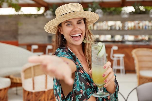 Szczęśliwa zrelaksowana turystka ubrana w letnią bluzkę i kapelusz, wyciąga rękę na pierwszym planie, siedzi samotnie w przytulnym barze z koktajlem lub napojem ze świeżych owoców. urocza zadowolona kobieta cieszy się kurortem