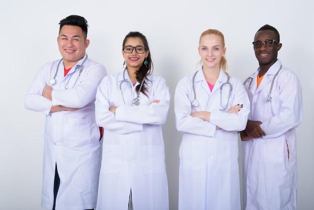 Szczęśliwa zróżnicowana grupa lekarzy wieloetnicznych, uśmiechając się z rękami skrzyżowanymi