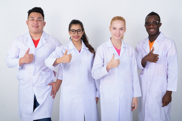 Szczęśliwa zróżnicowana grupa lekarzy wieloetnicznych uśmiechnięta i pokazująca kciuki do góry