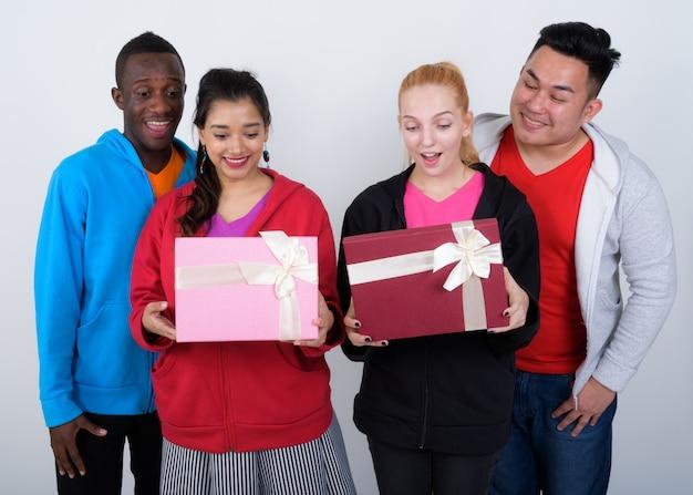 Szczęśliwa zróżnicowana grupa wieloetnicznych przyjaciół uśmiecha się podczas otwierania
