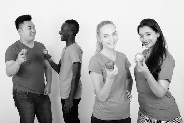 Szczęśliwa zróżnicowana grupa wieloetnicznych przyjaciół uśmiechających się, trzymających czerwone jabłko i pozujących razem z przyjaciółmi rozmawiającymi z tyłu