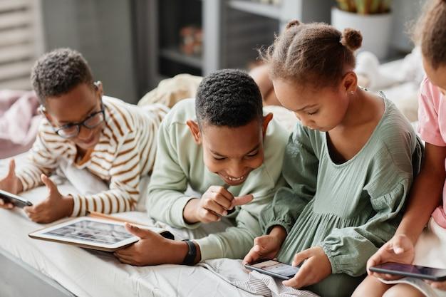 Szczęśliwe afrykańskie dzieci korzystające z gadżetów w rzędzie, leżąc razem w łóżku, kilkoro rodze...