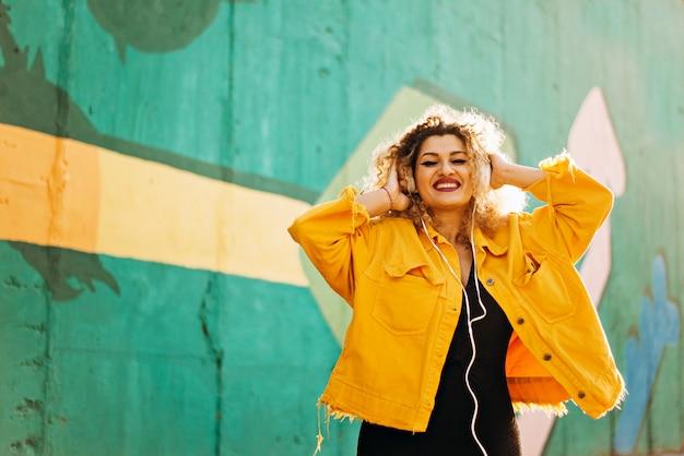 Szczęśliwe amerykańskie kobiety słuchają słuchawek muzycznych na kolorowej ścianie na zewnątrz