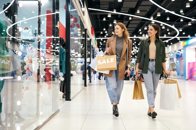 Szczęśliwe atrakcyjne dziewczyny w strojach casual chodzą po centrum handlowym i cieszą się razem na zakupach