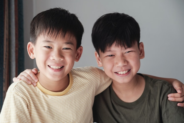 Szczęśliwe azjatyckie animacje chłopców uśmiechając się i przytulając się wzajemnie, portret chłopców preteen, przyjaźnie