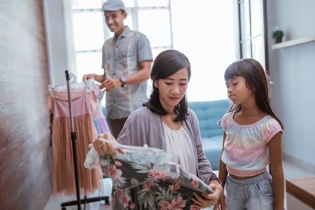 Szczęśliwe azjatyckie rodzinne zakupy w sklepie odzieżowym razem
