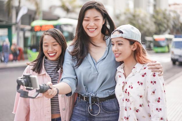 Szczęśliwe azjatykcie dziewczyny robi vlog wideo przy przystankiem autobusowym. modni przyjaciele blogujący dla mediów społecznościowych na zewnątrz