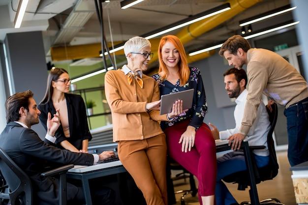 Szczęśliwe biznesowe kobiety pracuje wpólnie online na cyfrowej pastylce przy biurem
