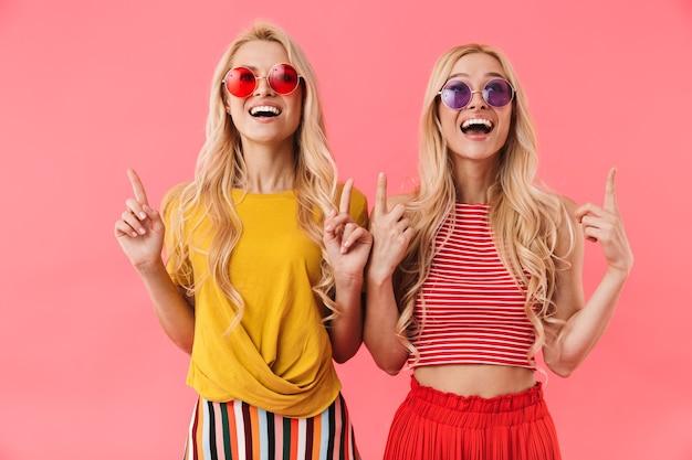 Szczęśliwe blond bliźniaczki w okularach przeciwsłonecznych, wskazujące i patrzące w górę z otwartymi ustami na różowej ścianie