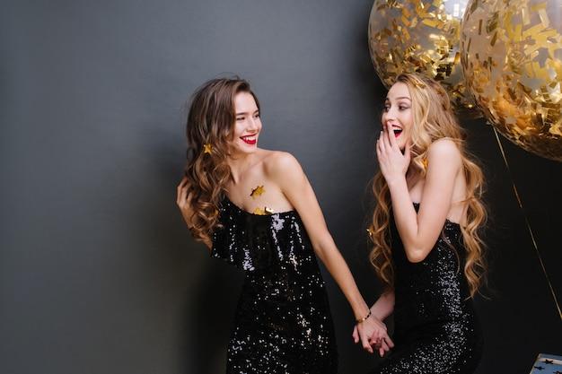 Szczęśliwe chwile imprezowe dwóch modnych śmiesznych młodych kobiet. luksusowa czarna sukienka, długie kręcone włosy, wesoły nastrój, dobra zabawa, uśmiech, wyrażanie pozytywności.
