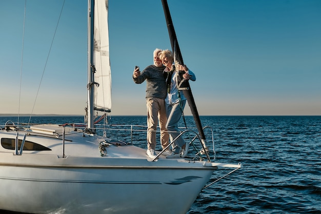 Szczęśliwe chwile pełnej długości pięknej pary seniorów robi selfie na smartfonie i uśmiecha się podczas