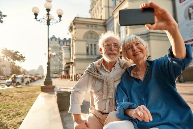 Szczęśliwe chwile wesoła starsza para w zwykłych ubraniach robi selfie siedząc na ławce