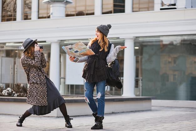 Szczęśliwe chwile zabawnych turystów w słoneczny dzień w dużym mieście. zabawne, radosne kobiety podróżujące razem, dobrze się bawiąc, robiąc zdjęcia, wyrażając prawdziwie żywe pozytywne emocje, stylowy wygląd, najlepsi przyjaciele.