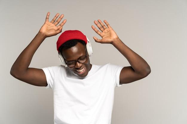 Szczęśliwe czarne męskie słuchawki bezprzewodowe, cieszące się słuchaniem muzyki tańczącej z podniesionymi rękami