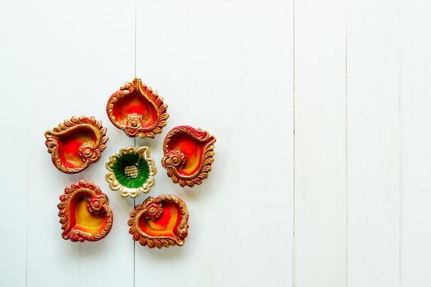 Szczęśliwe diwali, gliniane diya lampy zaświecały podczas dipavali, hinduski festiwal świateł świętowanie. kolorowa tradycyjna nafciana lampa diya na biały drewnianym