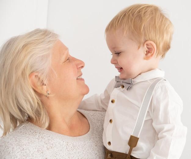 Szczęśliwe, dobrze wyglądające starsze kobiety z hir uroczym wnukiem kryty.