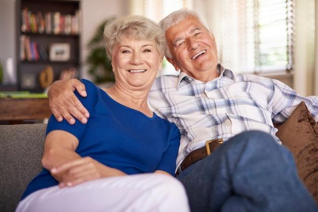 Szczęśliwe dojrzałe małżeństwo siedzi na kanapie