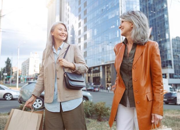 Szczęśliwe dojrzałe panie z torbami na zakupy spacerują po nowoczesnej ulicy miasta