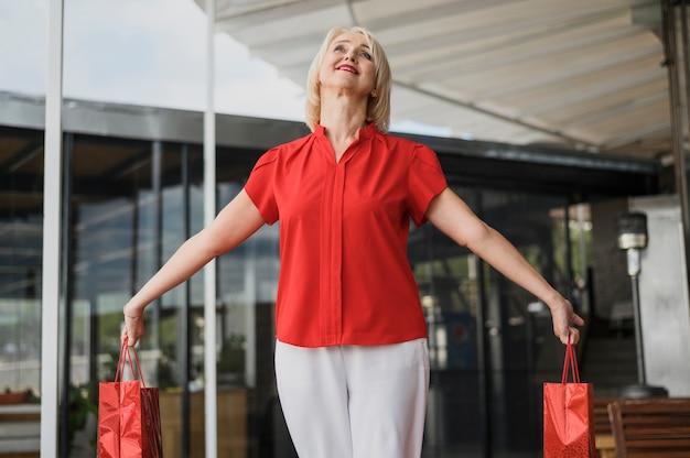 Szczęśliwe dorosłej kobiety mienia torba na zakupy