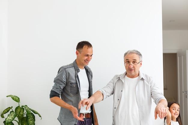 Szczęśliwe dwa pokolenia mężczyzn rodziny stary ojciec obejmując młodego dorosłego dorosłego syna bawiącego się przy użyciu inteligentnego wiązania telefonu oglądając śmieszne filmy w mediach społecznościowych za pomocą aplikacji mobilnych
