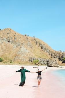 Szczęśliwe dwie azjatyckie kobiety w letnim kapeluszu spacerujące razem po różowej plaży