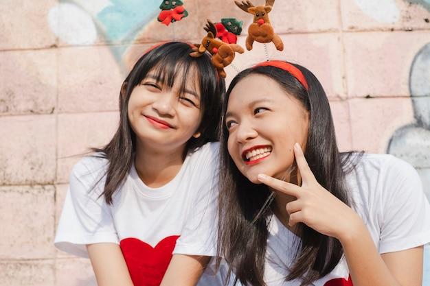 Szczęśliwe dwie dziewczyny noszą świąteczny kapelusz na kolorowym tle.