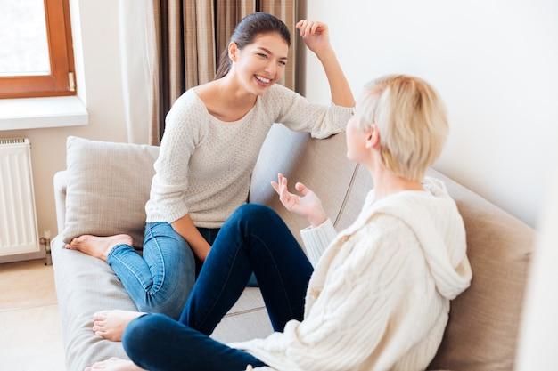 Szczęśliwe dwie dziewczyny siedzące na kanapie i plotkujące w domu