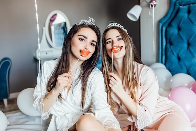 Szczęśliwe dwie młode kobiety trzymające karnawałowe akcesoria
