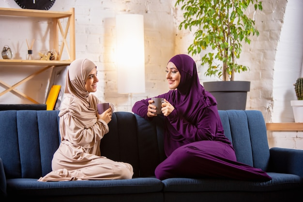 Szczęśliwe dwie muzułmanki w domu podczas lekcji, nauka przy komputerze, edukacja online