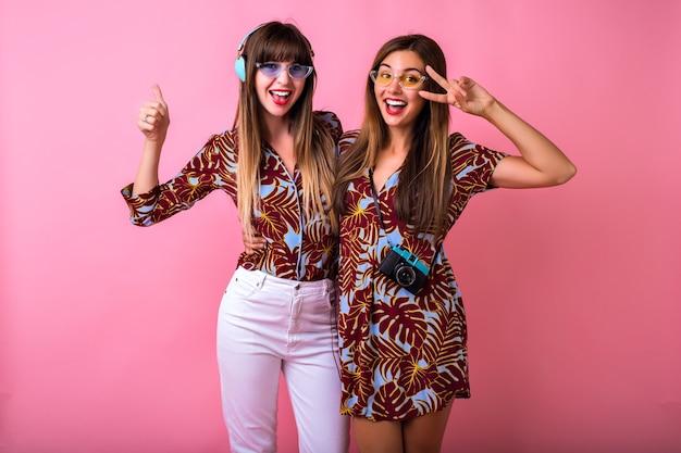 Szczęśliwe dwie najlepsze siostry przyjaciółki dobrze się bawią, pokazując ok nauki, pasujące kolorystycznie ubrania z tropikalnym nadrukiem, kolorowe, nowoczesne okulary przeciwsłoneczne, duże słuchawki i zabytkowy aparat, impreza studencka.
