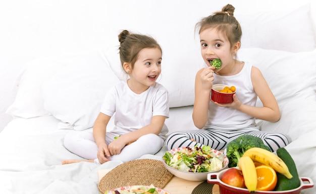 Szczęśliwe dwie słodkie dziewczyny jedzą owoce i warzywa w sypialni na łóżku. zdrowa żywność dla dzieci i młodzieży.