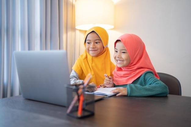 Szczęśliwe dwoje dzieci muzułmańskich noszenie chusty na głowie uśmiecha się podczas korzystania z komputera przenośnego w domu