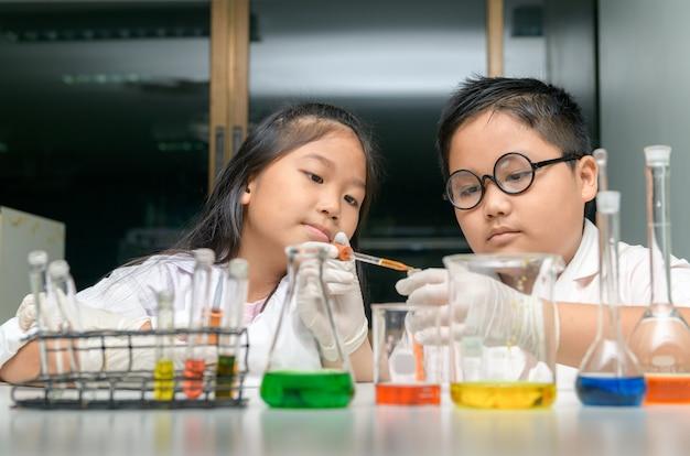 Szczęśliwe dwoje dzieci przeprowadzających eksperymenty naukowe.