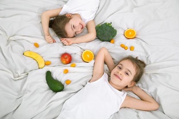 Szczęśliwe dwoje słodkie dzieci bawią się owocami i warzywami na łóżku. zdrowa żywność dla dzieci.