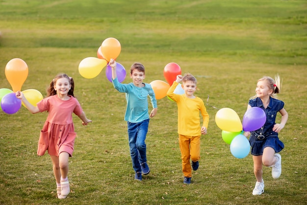 Szczęśliwe dzieci bawią się i biegają z balonami w parku wiosną