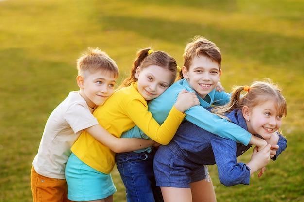 Szczęśliwe dzieci bawią się i odpoczywają w letnim parku.