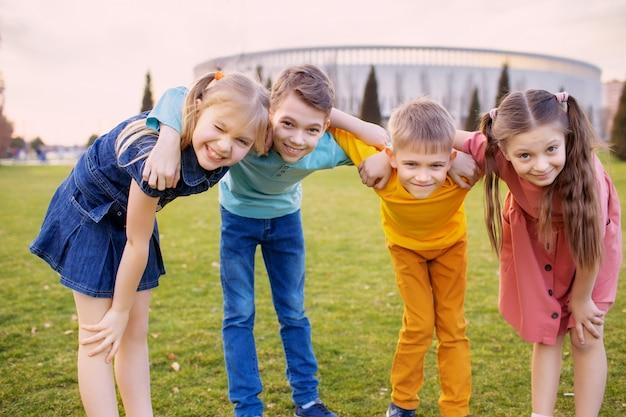 Szczęśliwe dzieci bawią się i relaksują w letnim parku