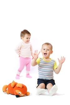Szczęśliwe dzieci bawią się pluszowym misiem.
