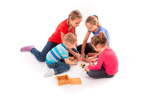 Szczęśliwe dzieci bawiące się blokami konstrukcyjnymi na białym tle. praca zespołowa, koncepcja kreatywności.