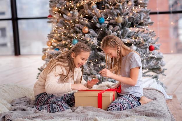 Szczęśliwe dzieci bawiące się i otwierające prezenty w pobliżu choinki.