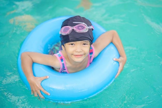 Szczęśliwe dzieci bawiące się na gumowym pierścieniu bezpieczeństwa do pływania w basenie