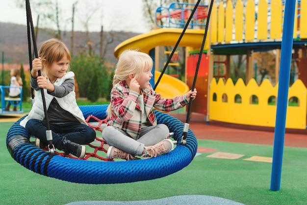 Szczęśliwe dzieci bawiące się na placu zabaw na świeżym powietrzu. najlepsze przyjaciółki grające razem.