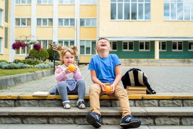 Szczęśliwe dzieci bawiące się na podwórku szkolnym w ciągu dnia. śniadanie w szkole, owoce i soki. stos podręczników, książek. szczęśliwa przyjazna siostra i brat
