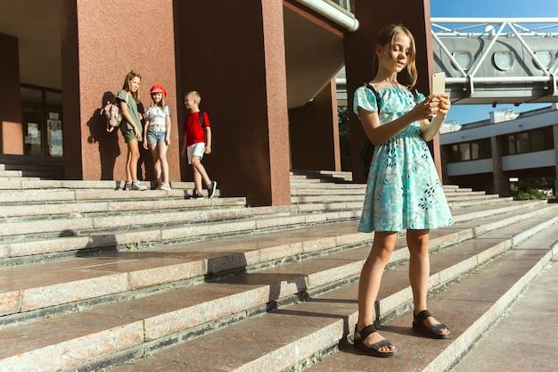 Szczęśliwe dzieci bawiące się na ulicy miasta w słoneczny letni dzień przed nowoczesnym budynkiem.