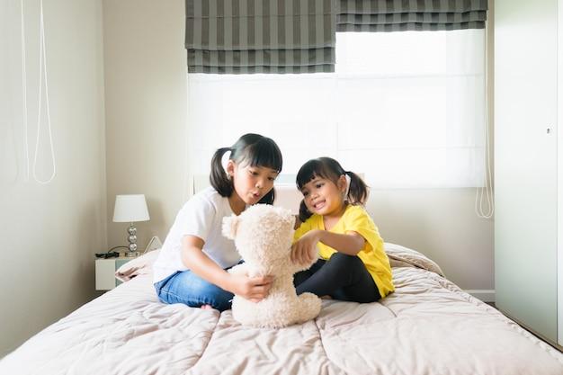 Szczęśliwe dzieci bawiące się razem w sypialni